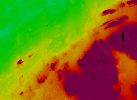 Seafloor bathymetry map of part of the Haig Fras site, showing rock outcrops (purple and red) surrounded by flatter sandy seabed (green).